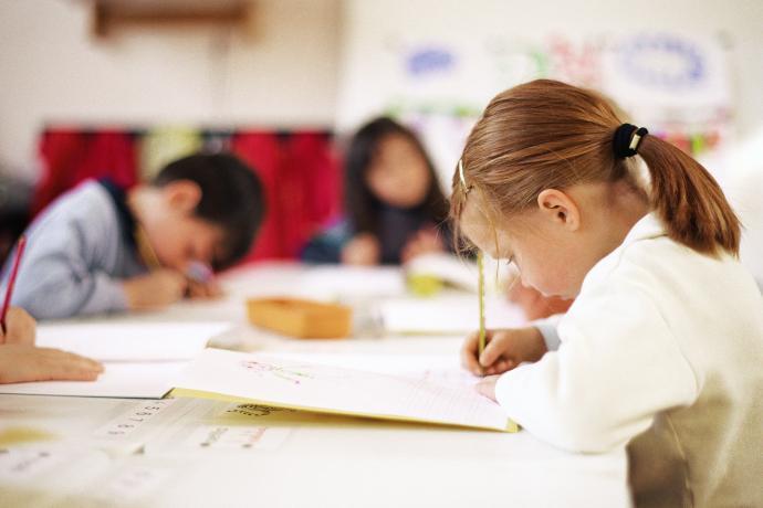to piger og en dreng der laver opgaver i et lyst klasseværelse